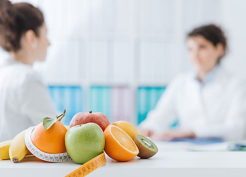 Female therapist cosulting with female client, selection of fruit and tape measure in foreground.
