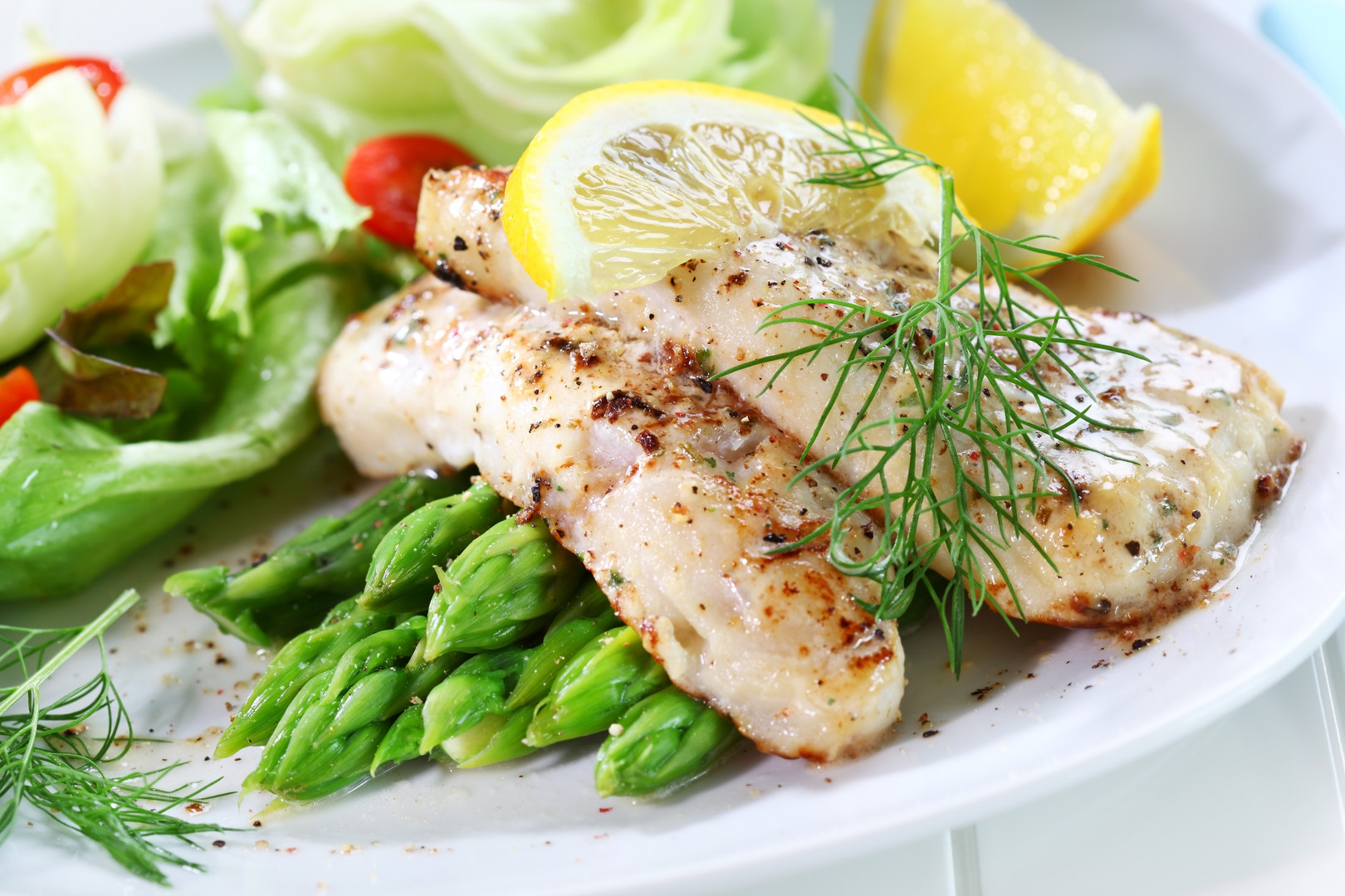 Fried fish on grilled asparagus with salad
