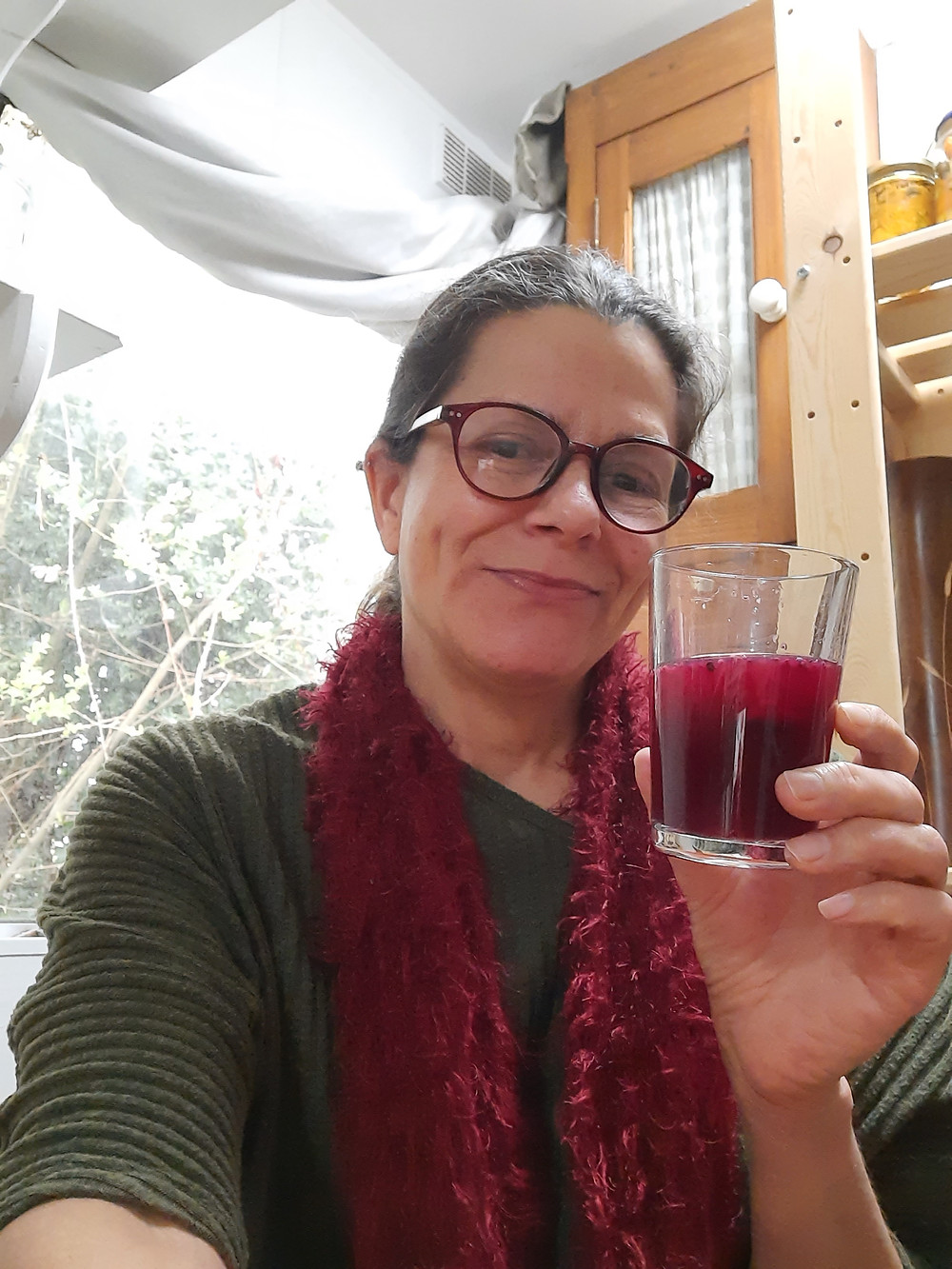 Woman holding glass of fermented purple carrot kanji with window in background