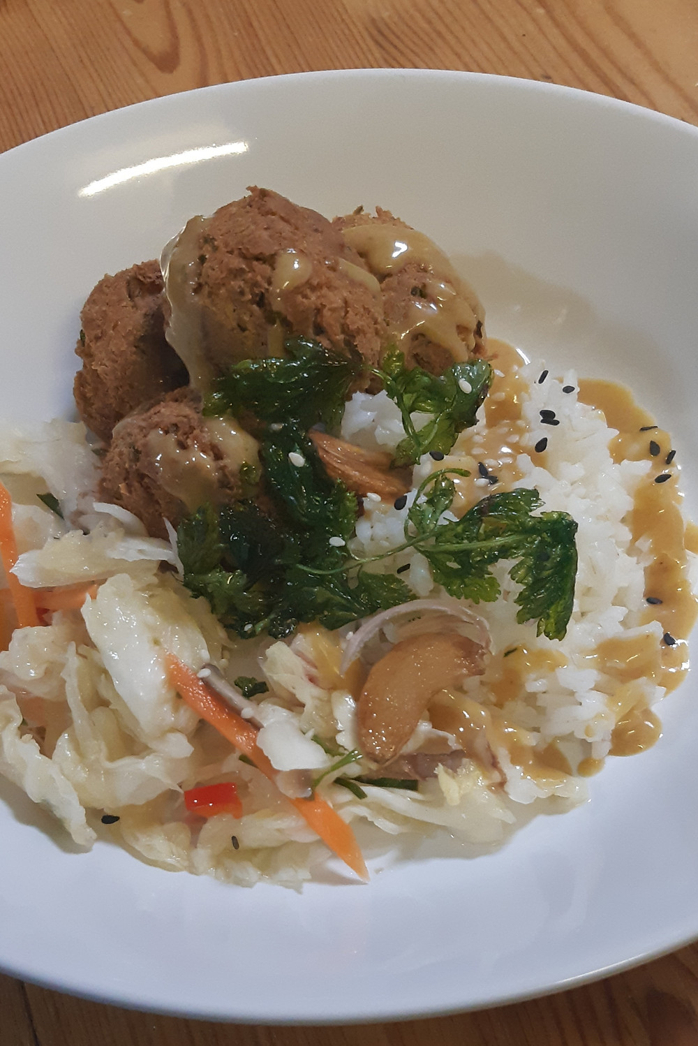 A plate of chickpea falafel, white kimchi and dressing