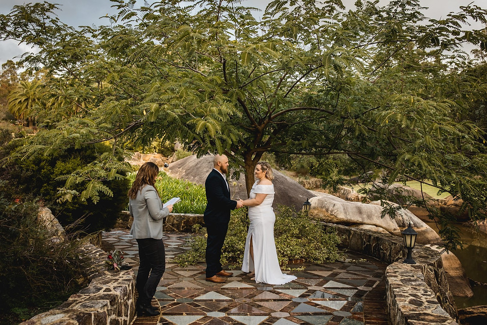 A bride and groom stand under a tree at a beautiful Airbnb property in the Perth Hills, with a celebrant officiating the ceremony