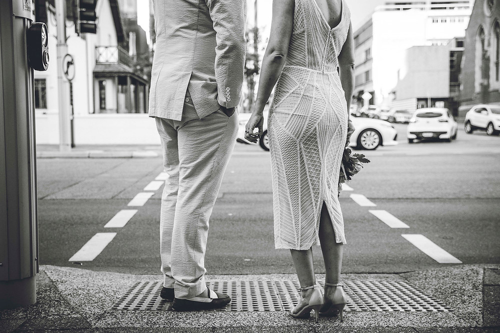 a groom in a suit and a bride in a short beaded gown and flowers, about to cross St Georges Tce in Perth City
