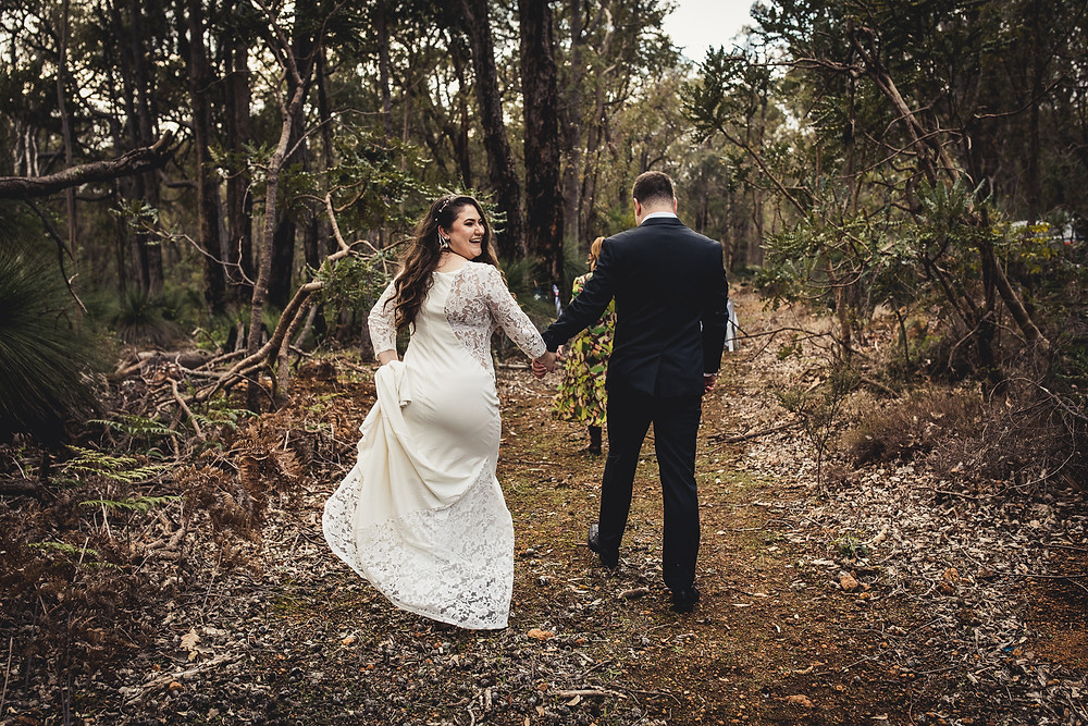 A bride and groom on a dirt track in the bush
