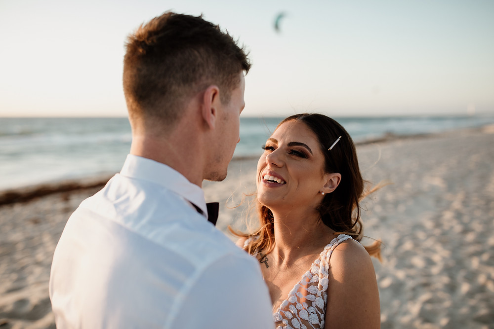 A bride and groom smile at each other while the sun goes down at Scarborough Beach Western Australia