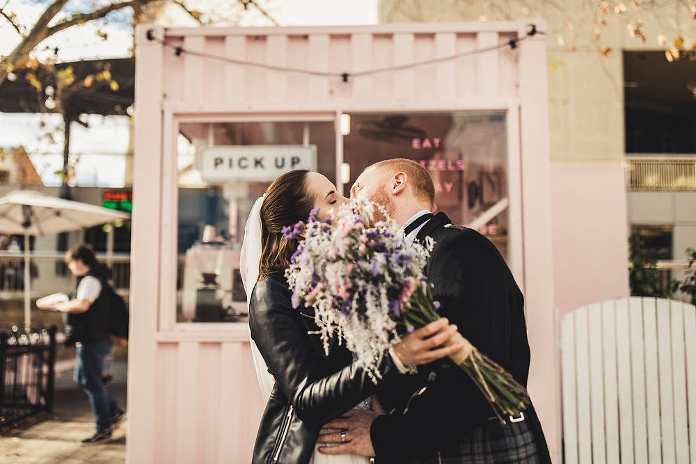 A bride wearing a leather jacket and a groom wearing a suit and kilt kiss in front of a pink pretzel sea container in Northbridge