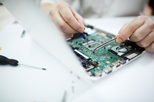 A closeup of a compuer circuit board with a technician's tools