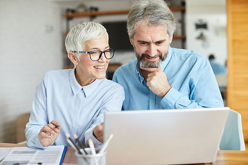 A man and woman with grey hair looking happily at their computer.