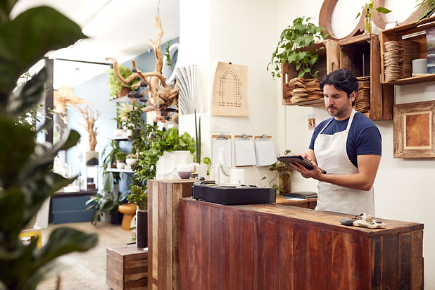 small business owner at counter with tablet needs data backup & recovery