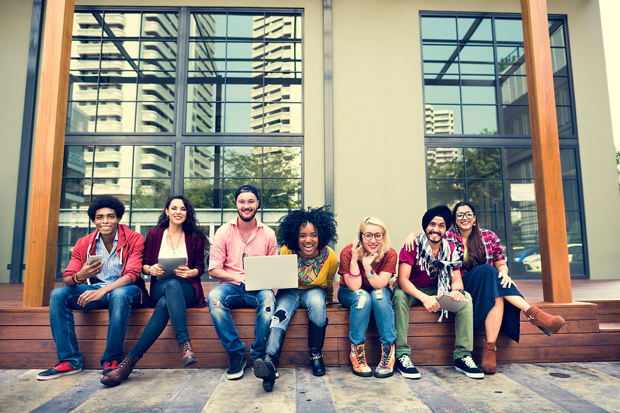 7 diverse college students seated outside a college building on a wooden platform