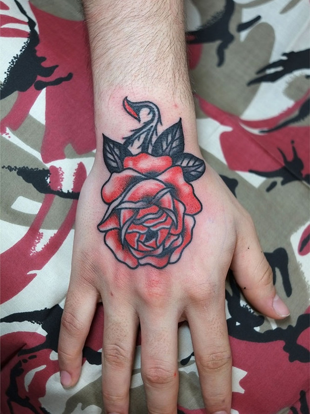 Red Rose tattoo on hand with thorns