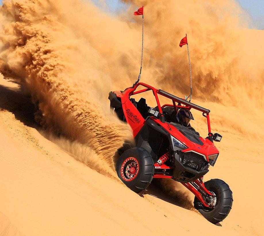 whip it light rods on a UTV driving on a sand dune