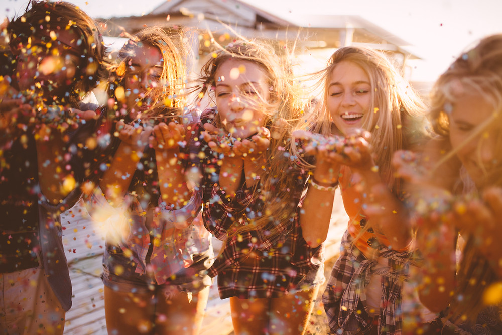 Image Description: A picture of five white female friends blowing confetti into the air. They are standing somewhere outside.
