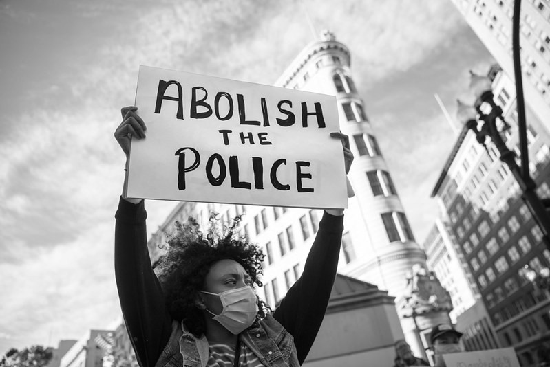 """A Black person holding a sign that reads """"abolish the police"""" in the foreground with buildings in the background."""