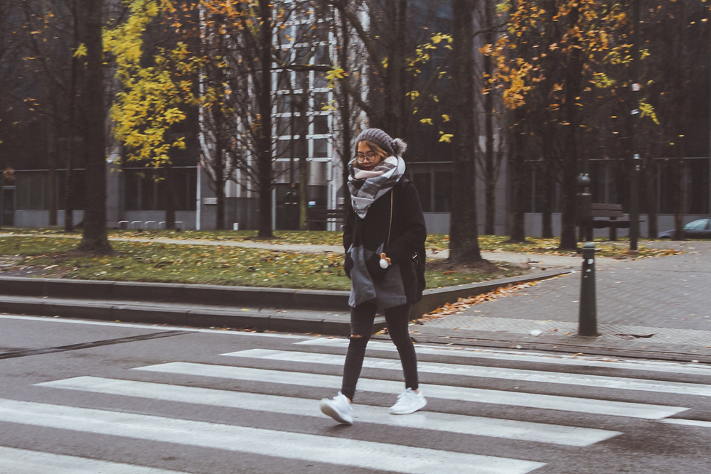 girl crossing the street asian winter outfit autumn leave street in Brussels Belgium Germany