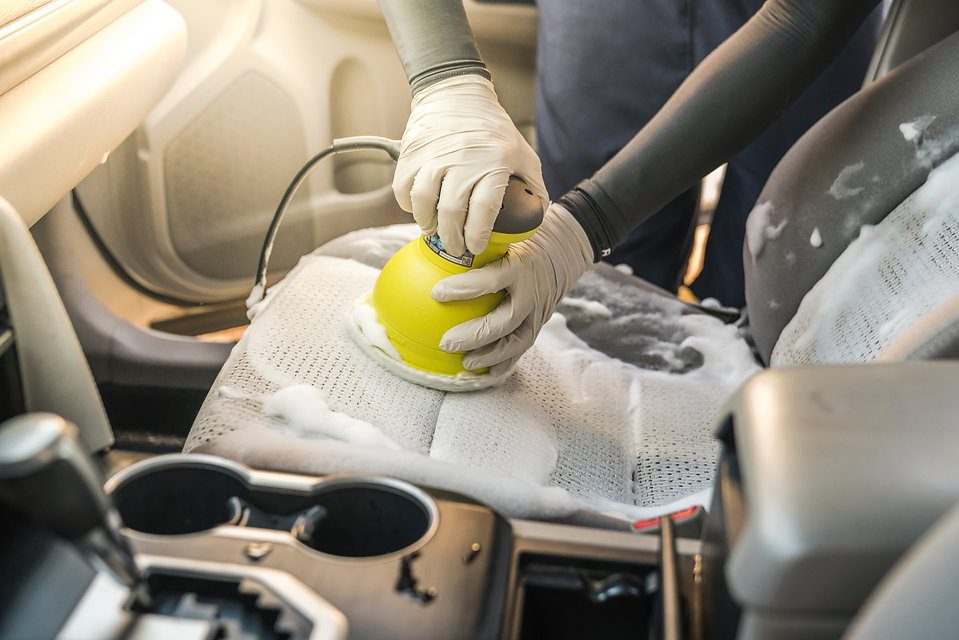 a man cleaning car interior by use foam