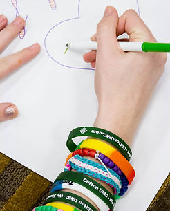 Student with multiple bracelets drawing a picture of a heart.