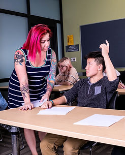 Teacher with pink hair helping a student with their hand up.