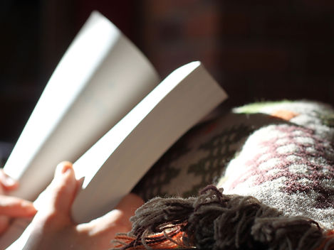 Person reading a book with a blanket