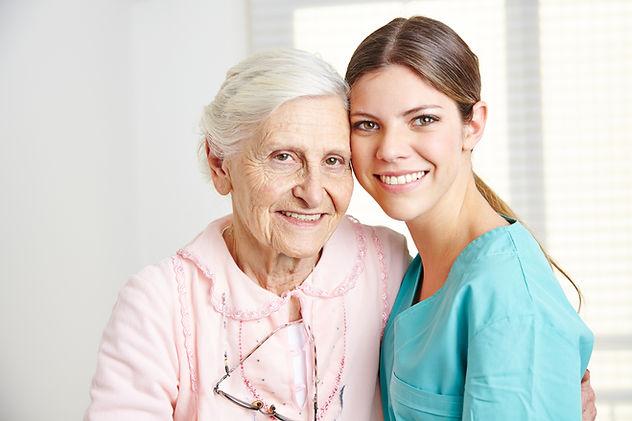 Smiling caregiver embracing happy senior woman in nursing home.jpg
