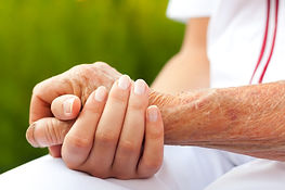 Doctor holding hand of an elderly woman.