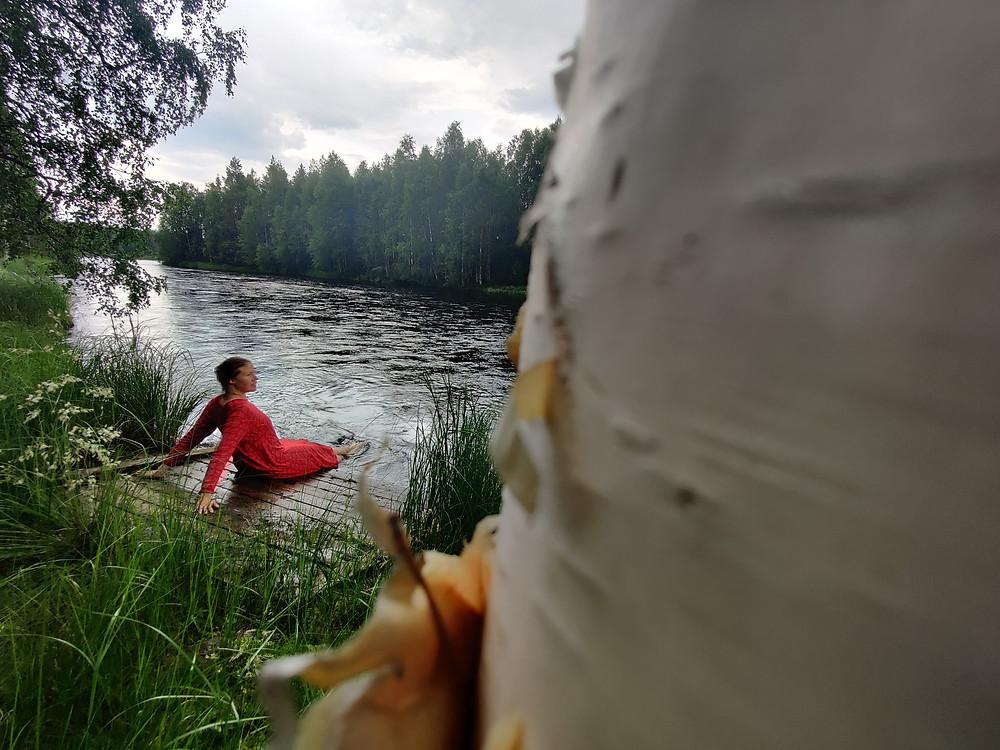 Koivurungon takaa näkyy tanssitaiteilija nauttimassa pienellä laiturilla kesästä jalat vedessä.