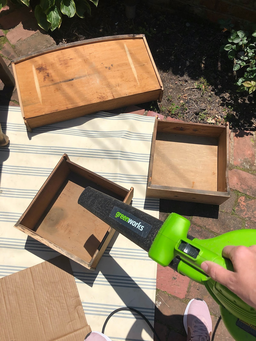 A greenworks leaf blower and pieces of a traditional nightstand that is being refinished.