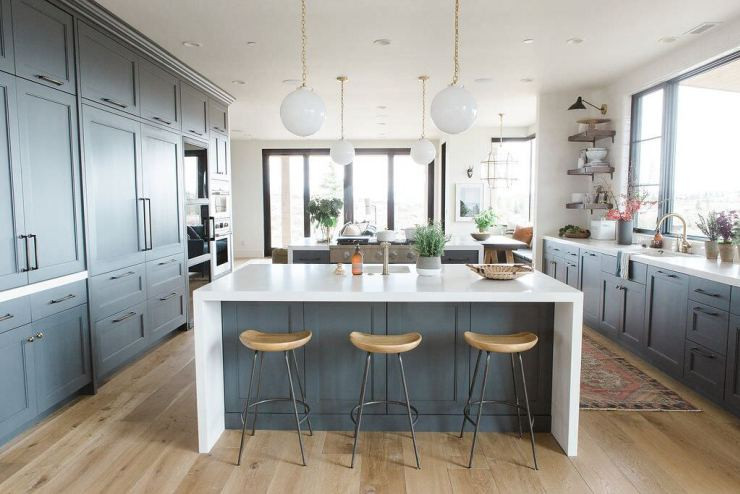 Modern+kitchen+with+white+waterfall+edged+countertops,+natural+wood+barstools,+and+dark+cabinets+in+Benjamin+Moore's+Cheating+Heart