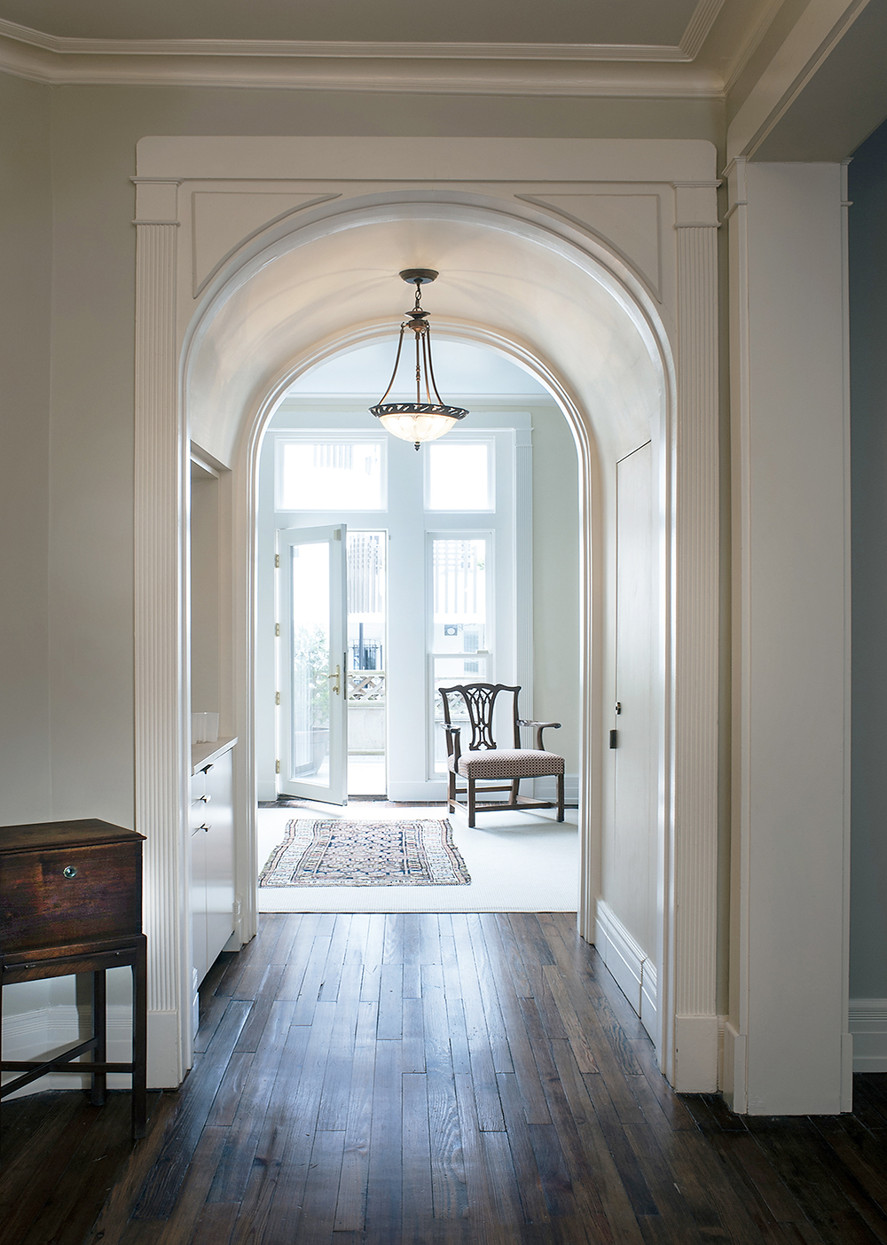 Beautiful arched hallway with pendant light and original wood floors.