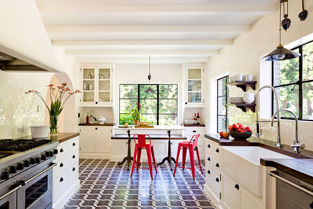 This black and white kitchen has large windows to bring the outdoor plants inside.