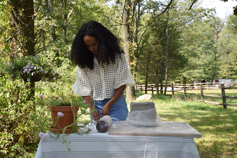 Ronni Nicole Robinson works on a craft on a table in a green field.