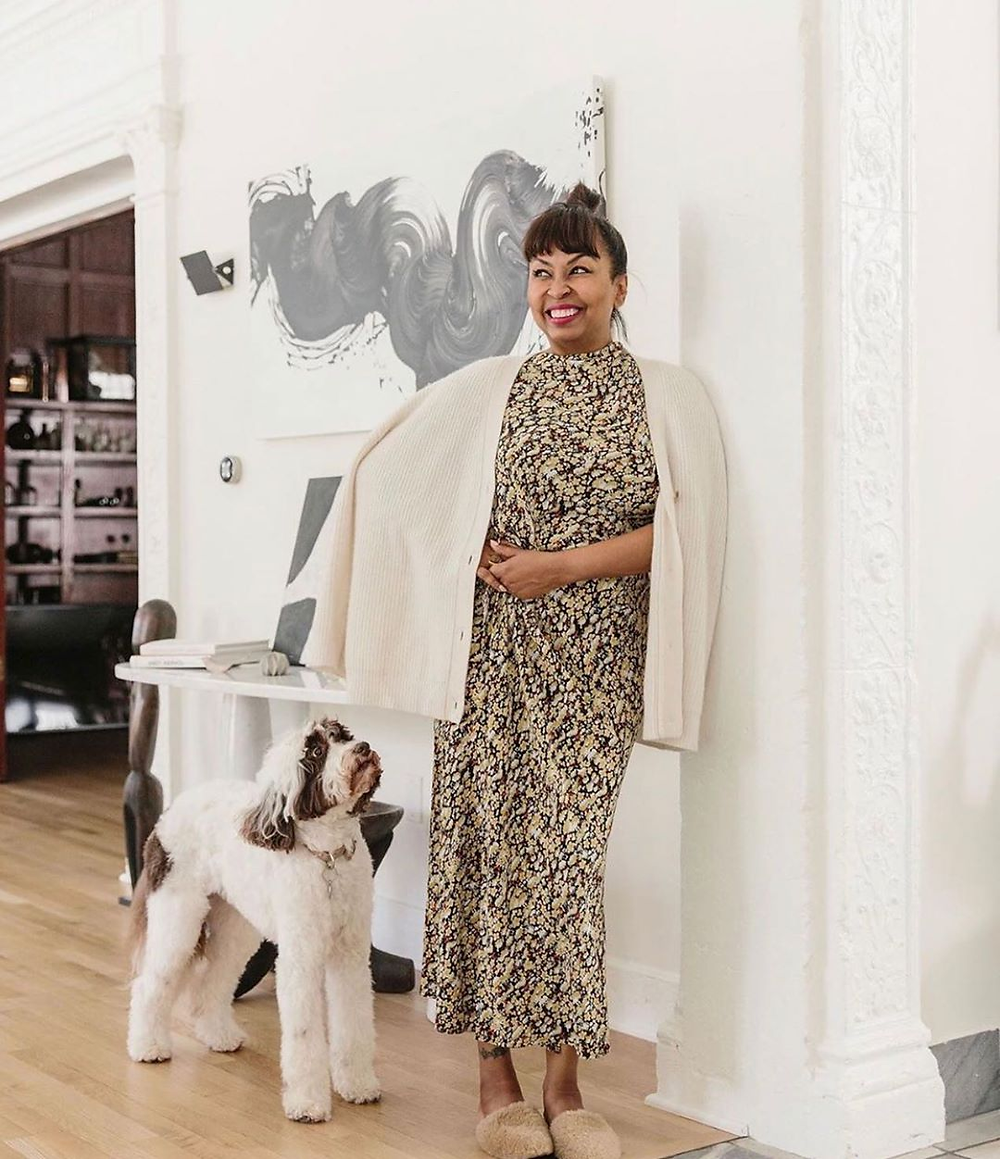 Brigette Romanek poses with her dog in a beautiful, modern home.