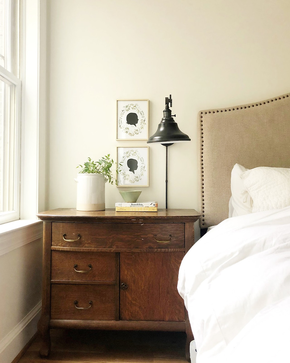 A traditional style vintage nightstand in a neutral, calming master bedroom.