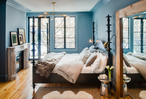 Pastel blue master bedroom with original fireplace and natural light.