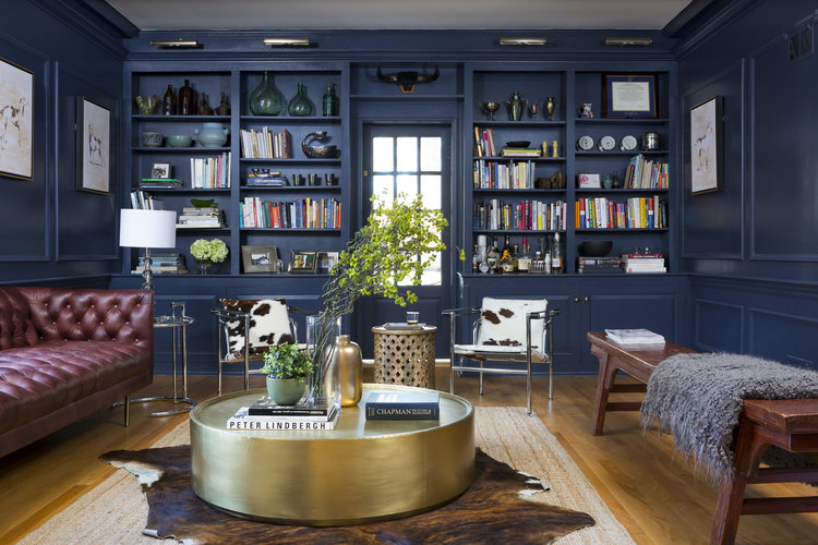 Moody blue study with tufted leather sofa, brass coffee table, and animal prints.
