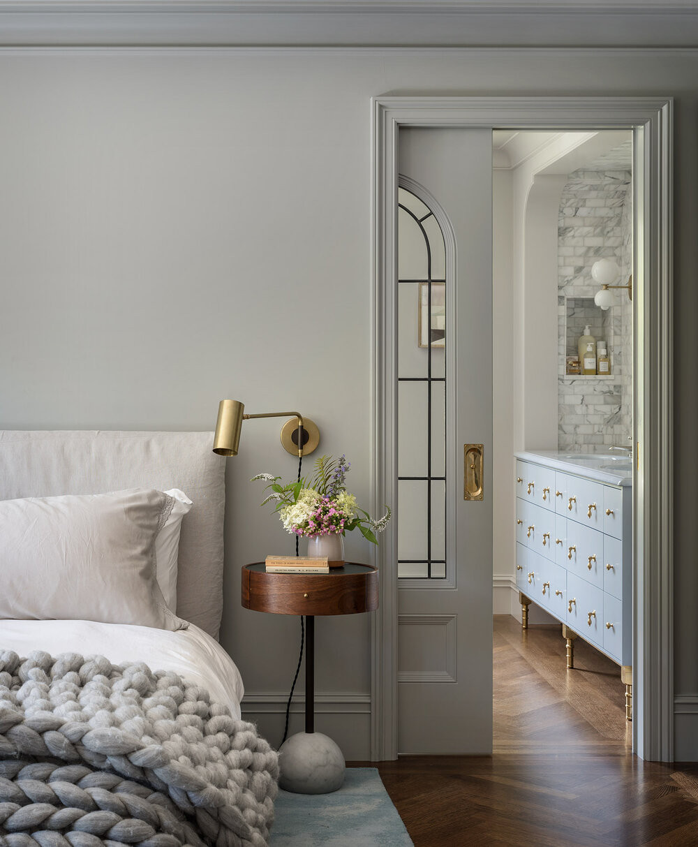 Beautiful neutral bedroom with arched pocket door.