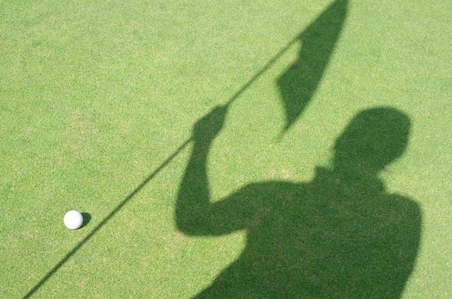 Golfer shadow hold flag on green golf.jp