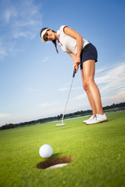 Smiling woman golf player putting succes