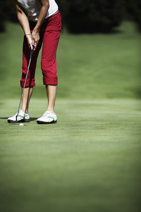Female golf player putting with ball jus