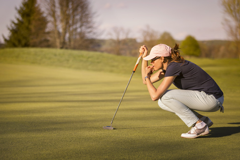 Woman golf player crouching and study th