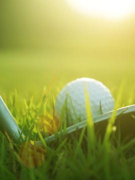 Blurred golf club and golf ball close up