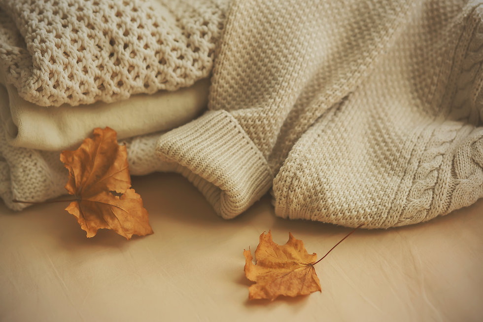 On a beige background are white woolen warm knitted sweaters, and next to them are two dr