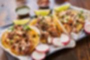 three street tacos in yellow corn tortil