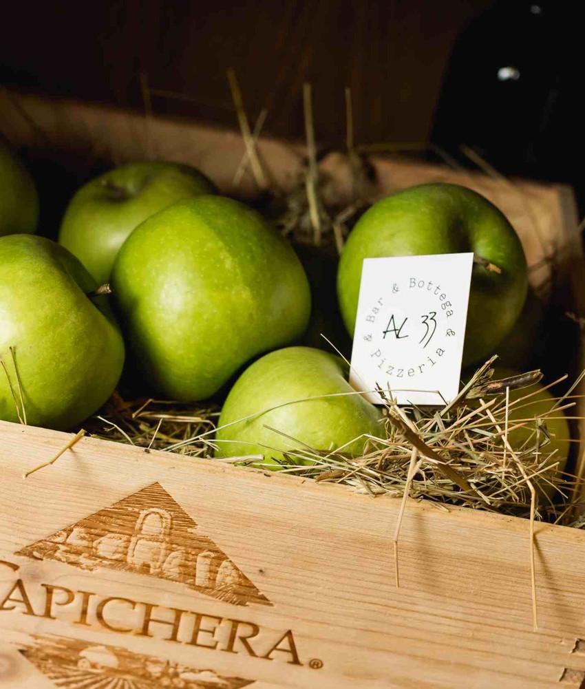 Декоративная инсталляция из винного ящика, соломы и свежих зеленых яблок с визиткой AL33 Pizzeria, Bar & Bottega.