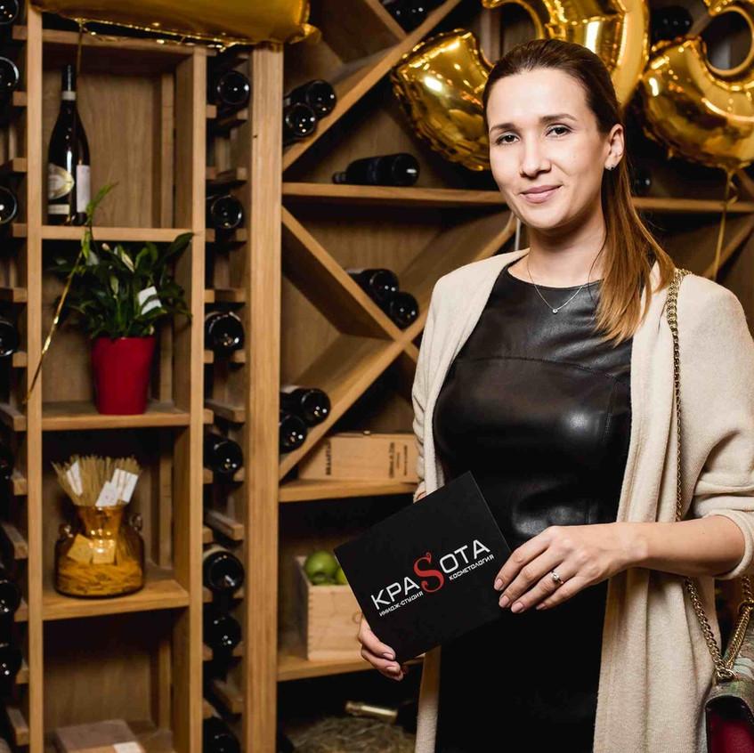 Девушка гостья торжественного мероприятия по случаю запуска нового итальянского ресторана AL33 на Динамо, получила сертификат от люксового салона красоты имидж студии КраSота! На фоне видна стена из деревянных полок для винных бутылок. Великолепный интерьер кафе восторгает!