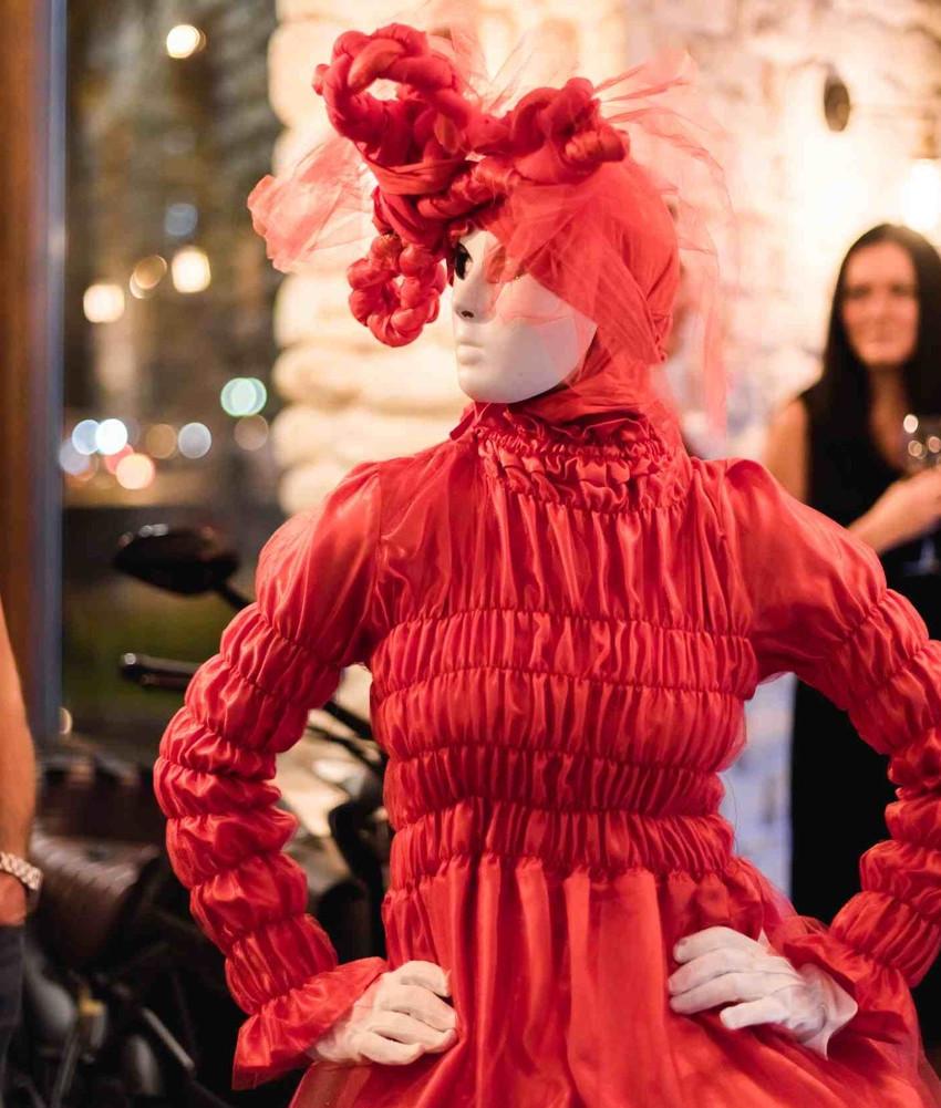 Модель маскарад в красном наряде на открытии пиццерии кафе AL33. Белая маска.