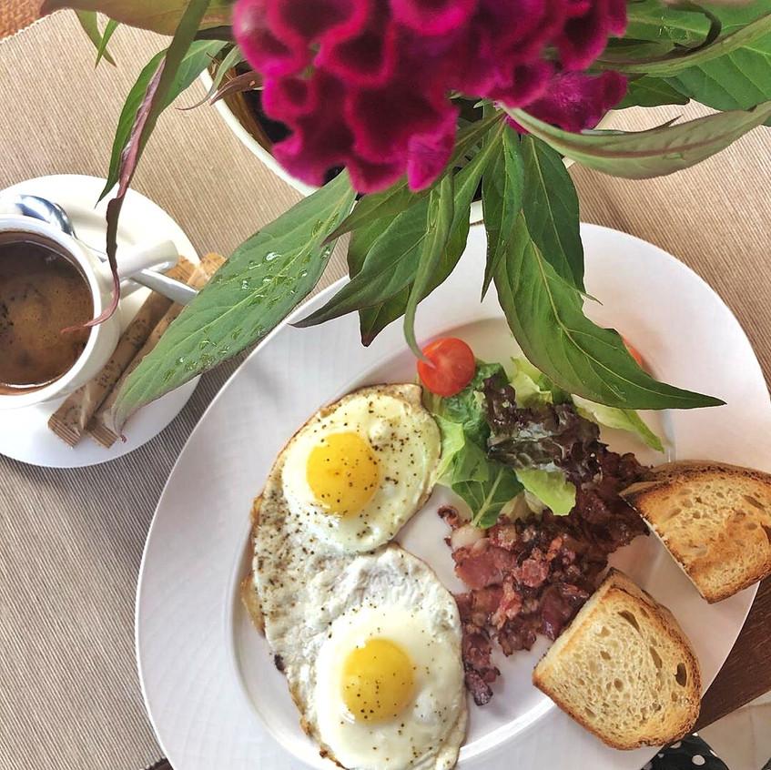 Прекрасный завтрак состоящий из яичницы-глазуньи с беконом и чашечки свежесваренного кофе на летней веранде итальянского ресторана-пиццерии AL33 в Москве на Динамо.