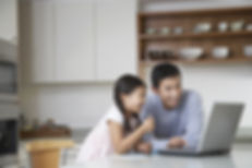 Father and daughter at computer having fun