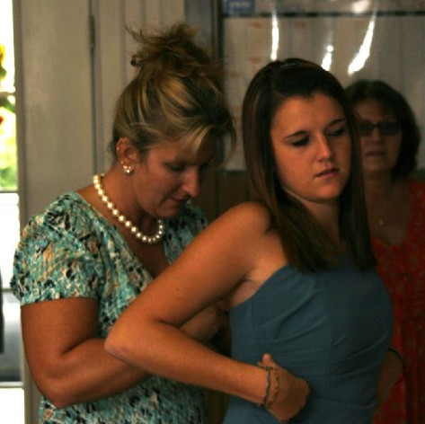 A mother helps her daughter zip up her dress for a wedding
