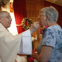 A catholic priest offers communion to an attendee at a wedding