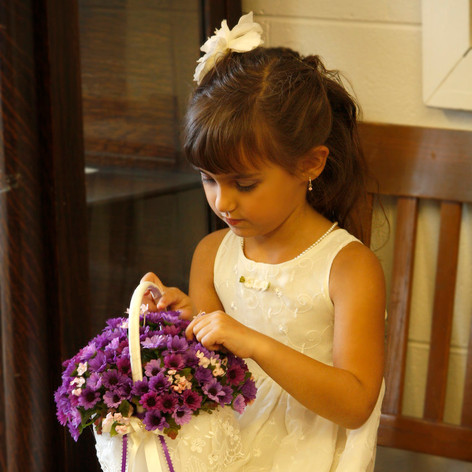 a flower girl picks at her bouquet while waiting to walk down the aisle